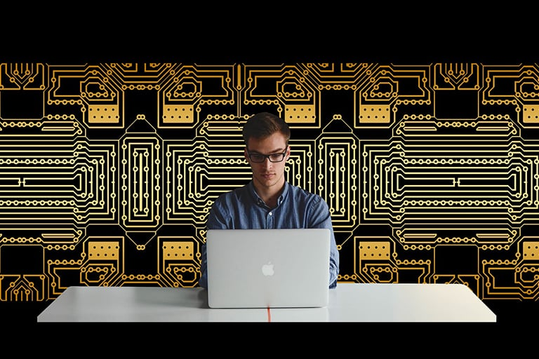 A man at a computer with circuit boards behind him.