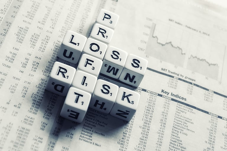 A newspaper with stock prices shown and dice on the newspaper with letters that spell out Profit, Loss and Risk.