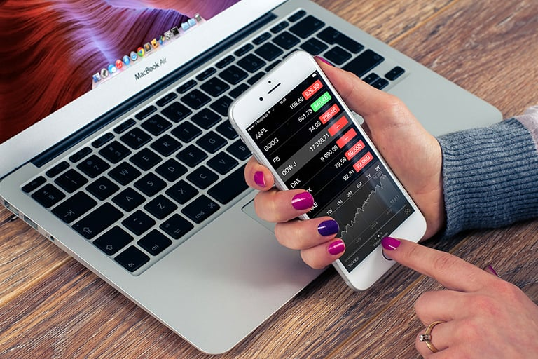 A lady holding open her iphone looking over stocks.