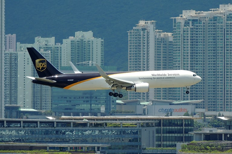A airplane with the UPS logo on its take, flying into an international airport.
