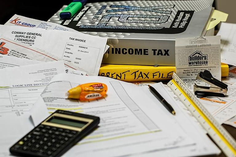 A desk of paperwork with a calculator and a income tax textbook next to it.