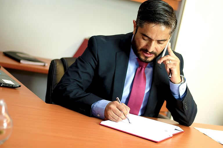 An attorney in an office writing down some notes while on the phone.