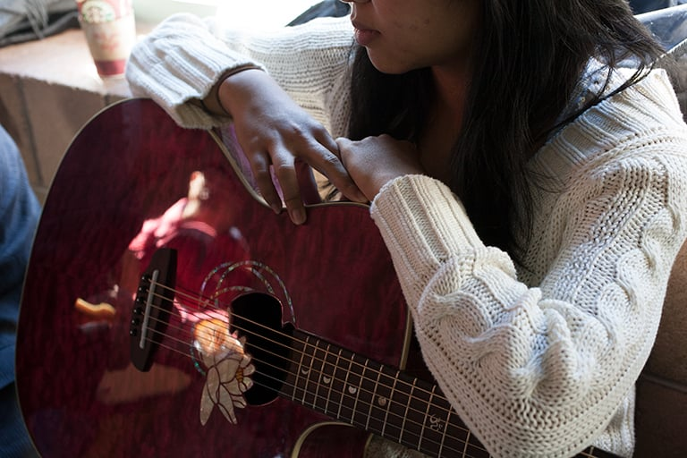 A student holding a guitar.