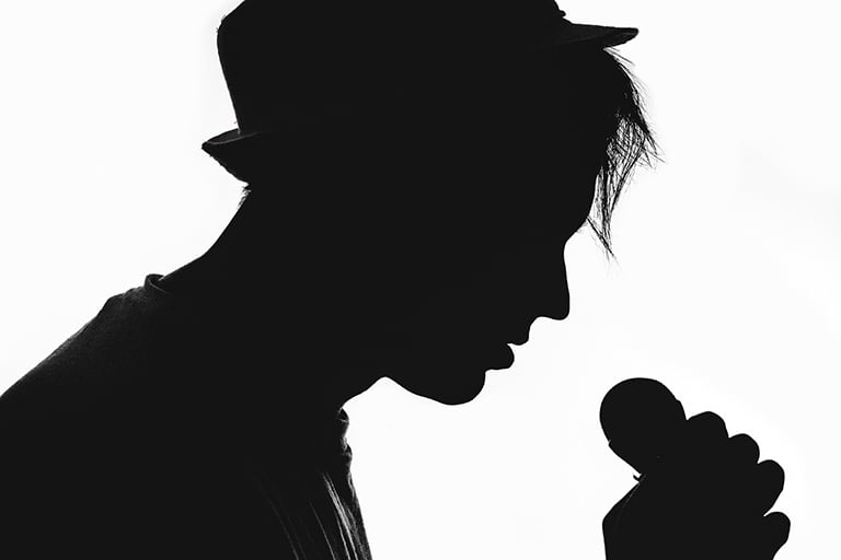 A silhouette of a celebrity holding a microphone.