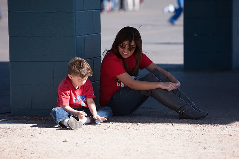 A social worker sitting and talking with a child on a playground.