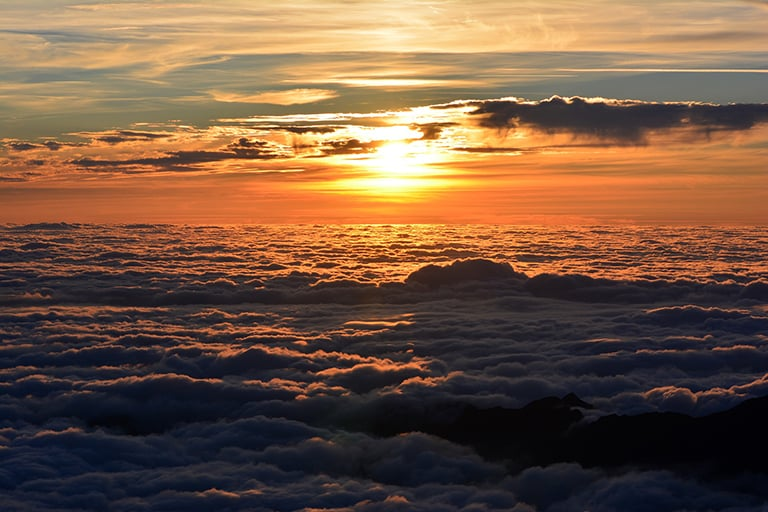 A sunset over a sea of clouds.