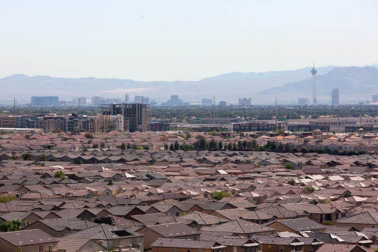 An image of the city of Las Vegas, with the strip in the horizon and residential homes below.