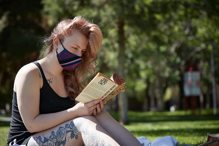 Student in mask, reads outside