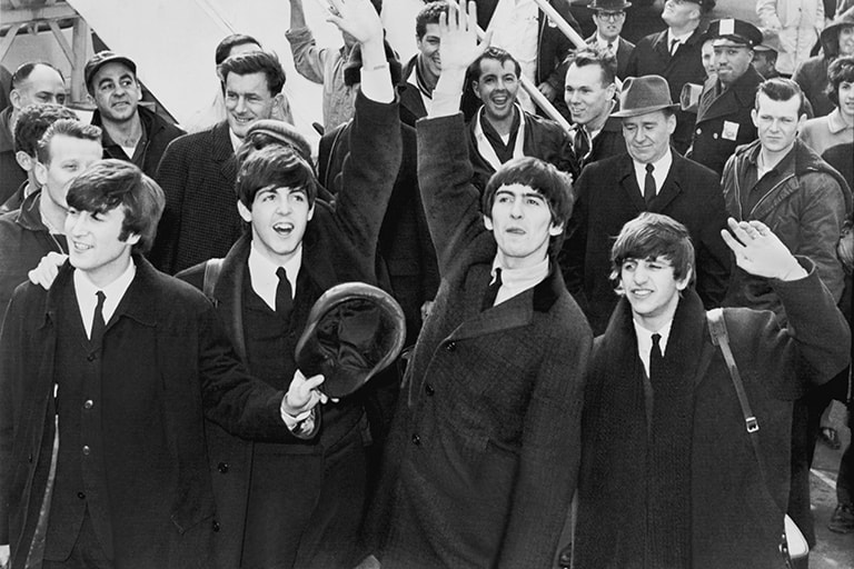 Members of The Beatles wave to crowd