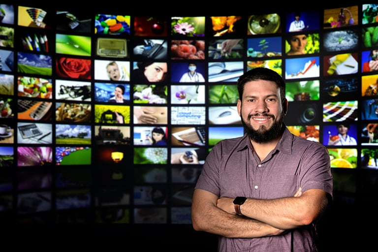 Man stands in front of a wall of television screens