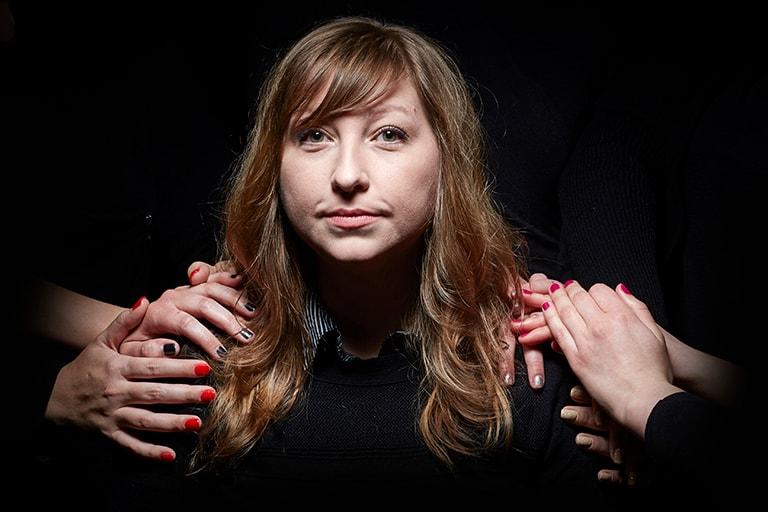 Jennifer Guthrie, under spotlight, with several hands on her shoulders