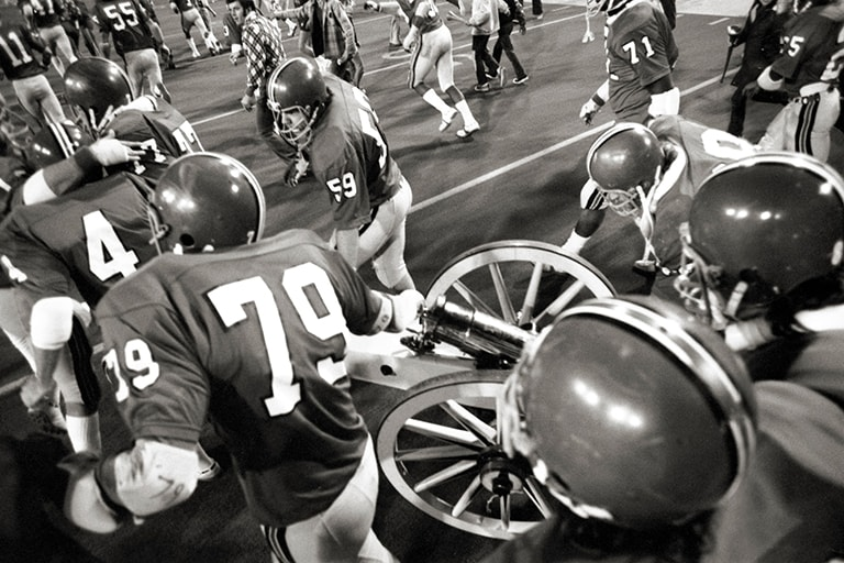 Black and white photo of football players wheeling cannon onto field.