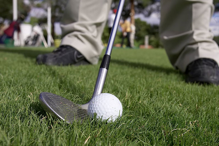 Closeup of golf club next to ball
