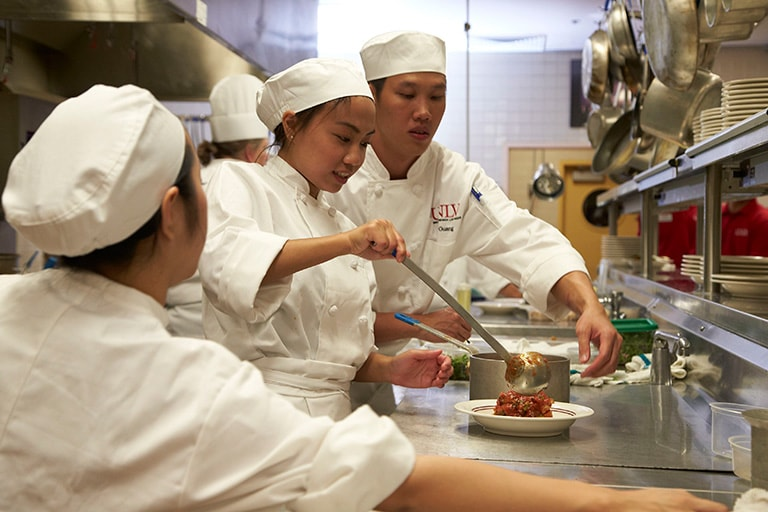 culinary students from Singapore work in the Boyd Dining Room kitchen
