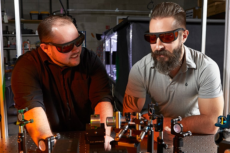 Two students work with laser equipment