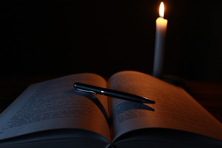 Open book with candle in behind it