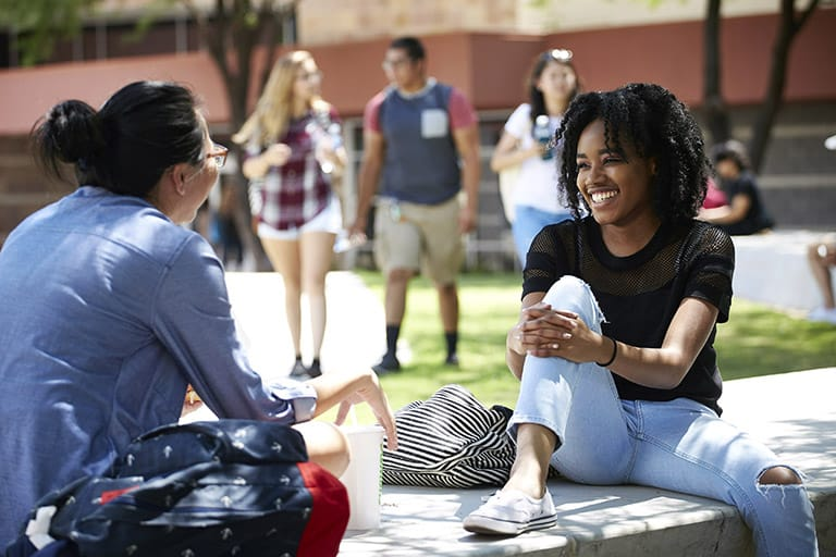 Two students sitting outside smiling at each other