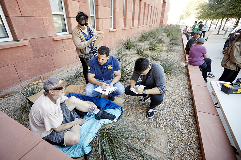 A group of students interviewing a man sitting on the ground