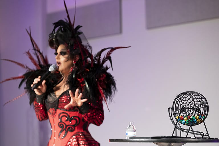 Bingo host on the left wearing an elaborate black and red dress, bingo cage with various colored ball inside