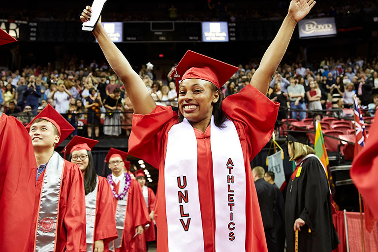 Female student at a commencement ceremony wearing a red graduation gown and a U-N-L-V Athletics sash.