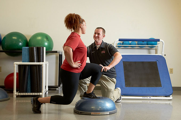 Male athletic trainer working with a female patient's balance