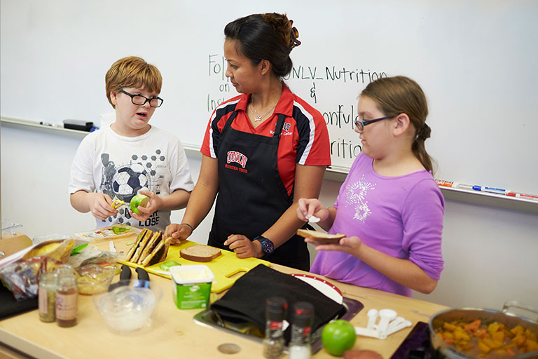 Female student working with two younger children to cook a well-balanced food dish