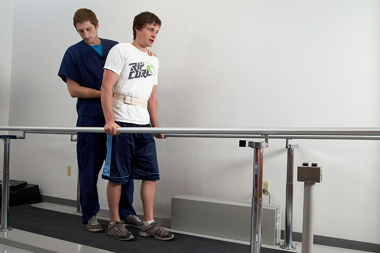 Male physical therapist assisting a patient with re-learning how to walk