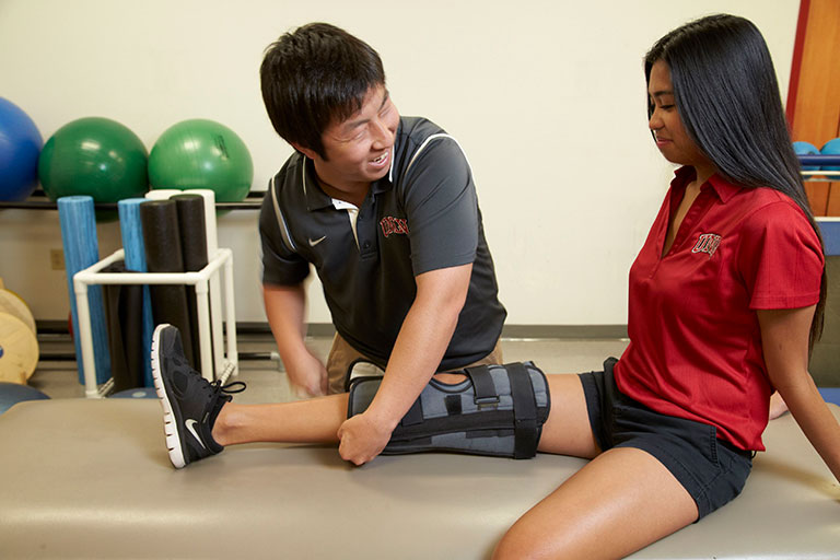 Male athletic training student working on a female student's knee