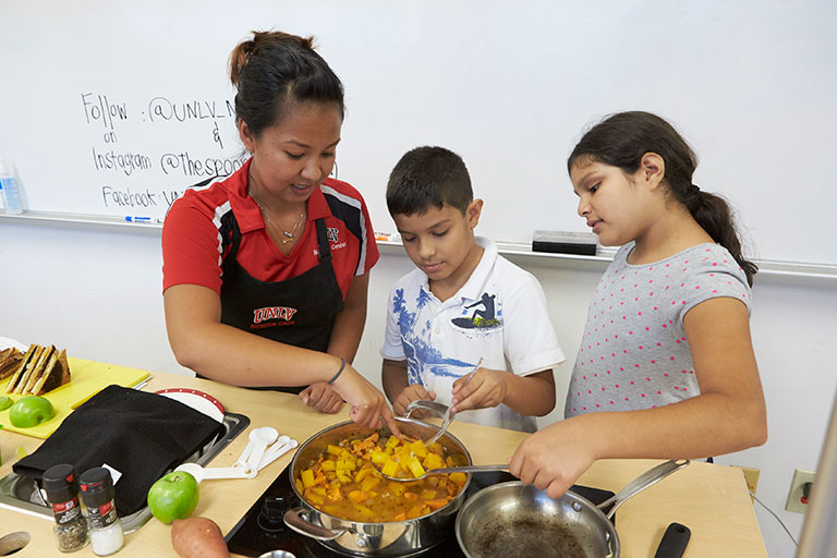 Female student working with two young children to cook a well-balanced dish