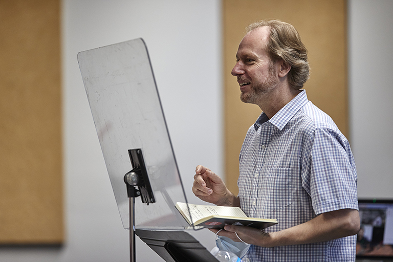 Professor holding an open book during a lecture or presentation