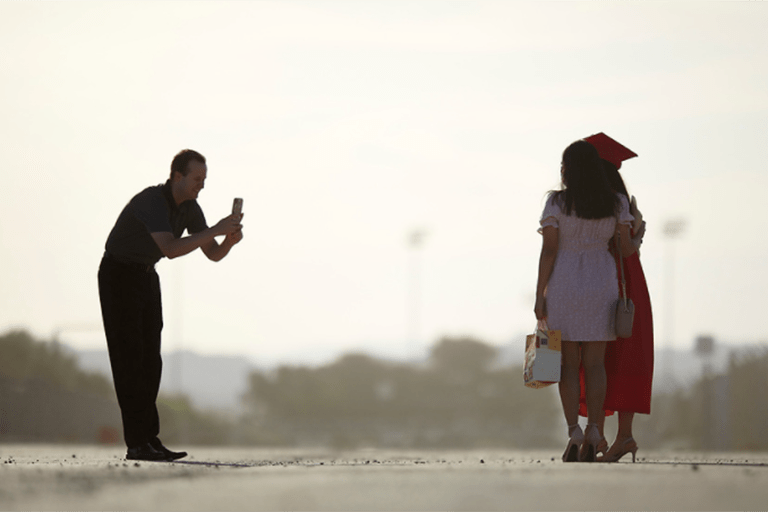 Man taking photo of a student wearing a graduation cap and gown posing with another person