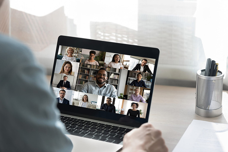 Open laptop with a video chat filled with numerous people shown on the screen