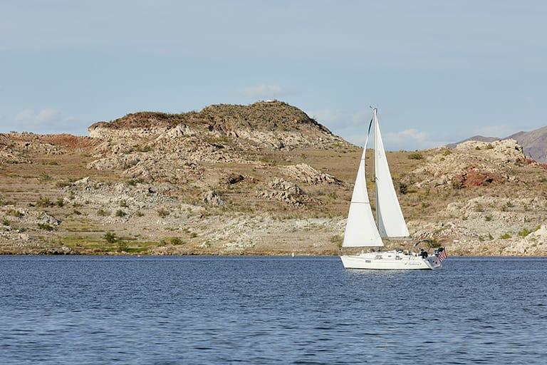 Sail boat on the water with desert hills in the background