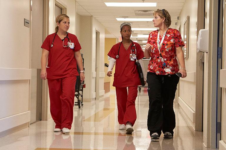 Three nurses walking down a hallway