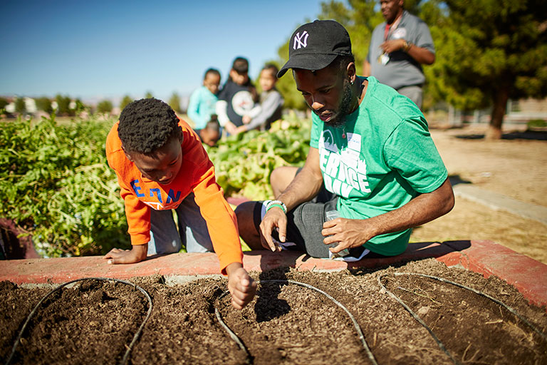 Male student in a green shirt and N-Y hat working with a young child to plant a garden