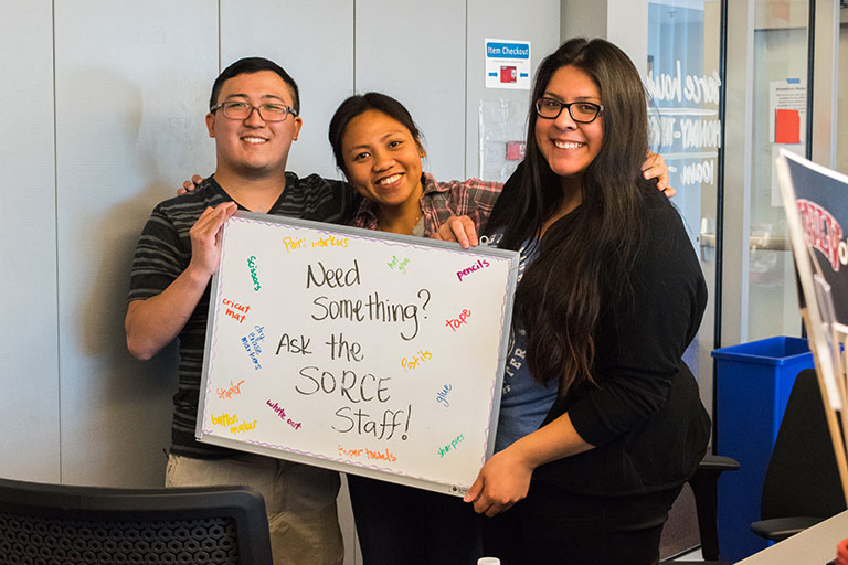 Three S-O-R-C-E staff members holding a white board that says 'Need Something? Ask the S-O-R-C-E Staff!'