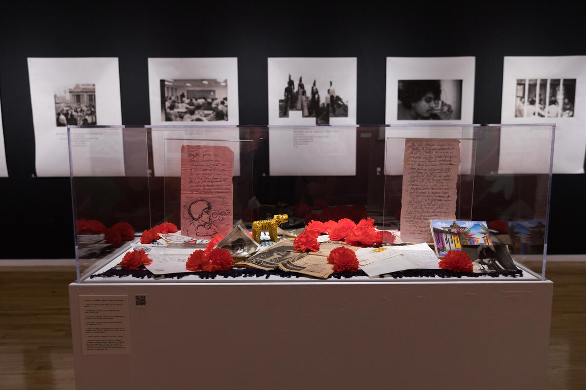 art exhibition of black and white photographs and a pedestal filled with personal items and red flowers
