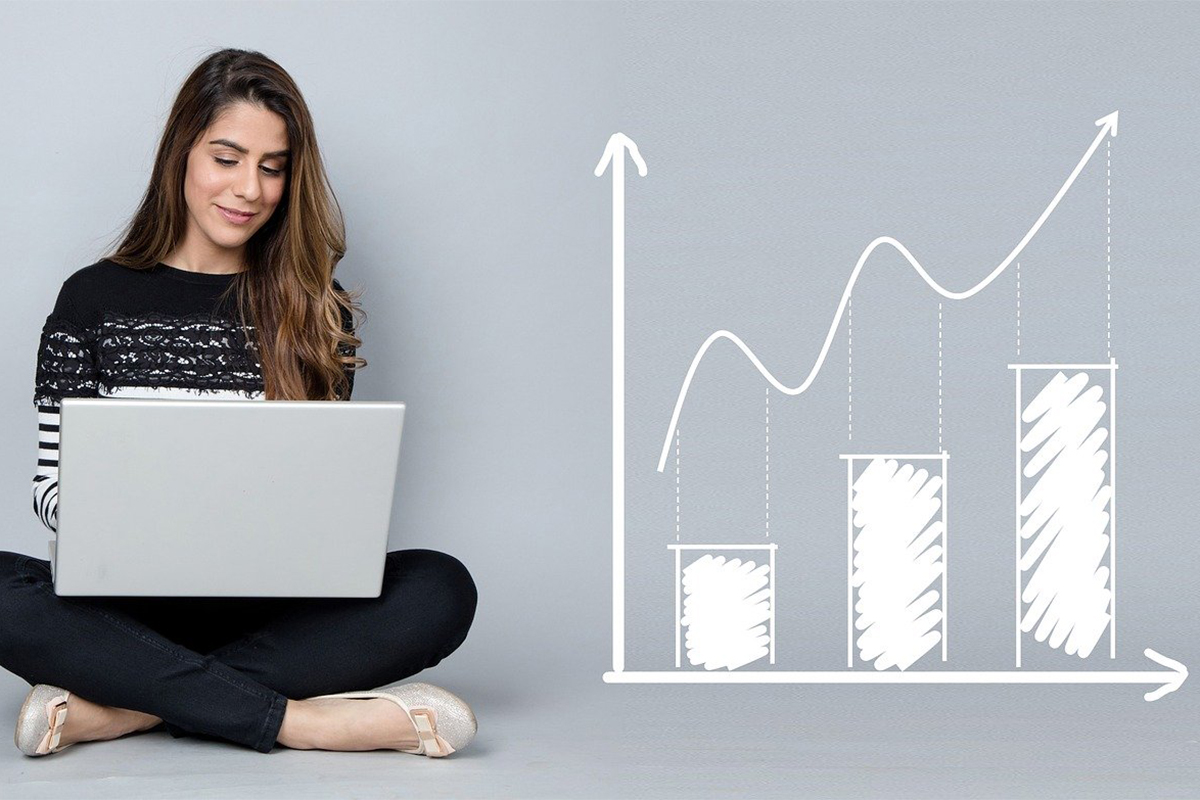 Girl sitting with a laptop next to a bar graph