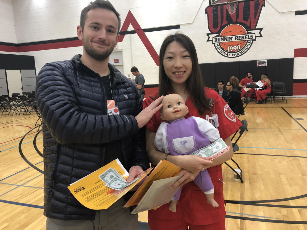 Two UNLV students with baby doll