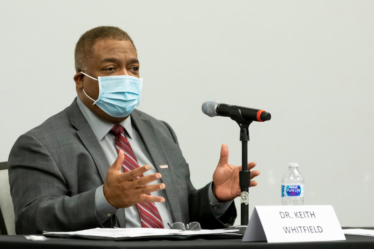 Dr. Keith Whitfield seated at table speaking into microphone