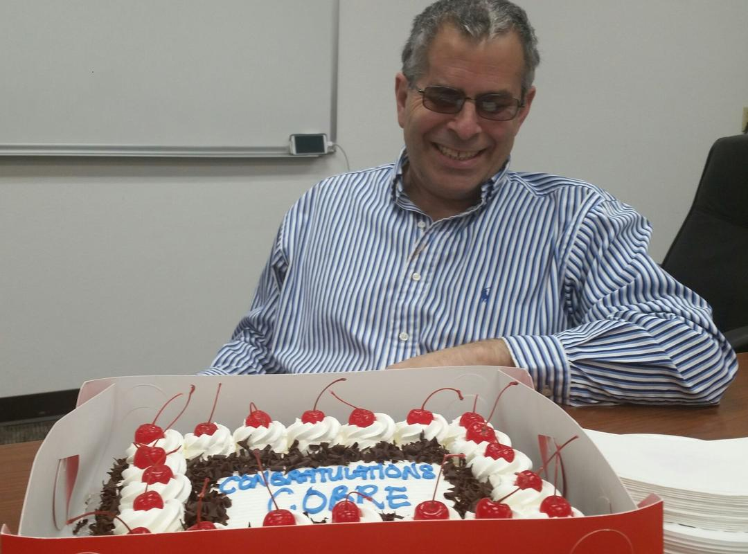 Martin Schiller smiling in front of a cake