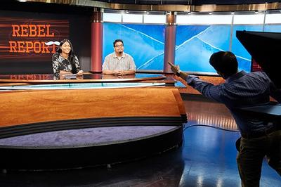 Two students at the anchor desk at the UNLV TV studio.