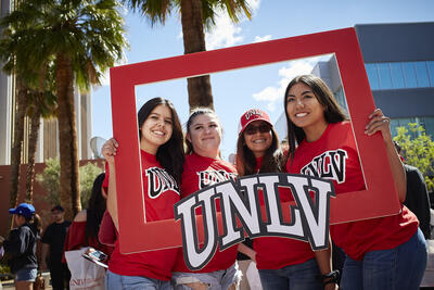 A picture of three students holding a UNLV signg.