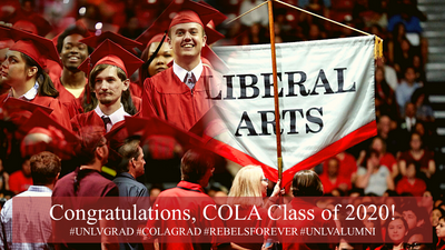 UNLV graduates in red caps and gowns, faculty holding liberal arts sign