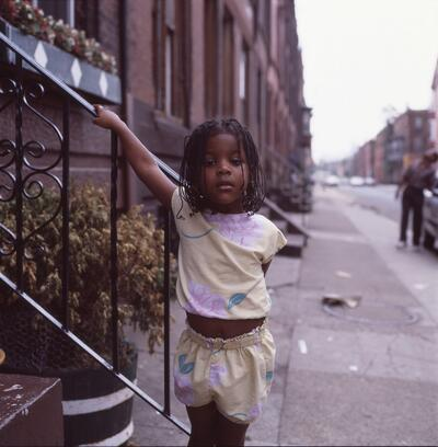 A young Black girl with braids looks directly at the camera while she holds onto the railing of a brownstone stair step.