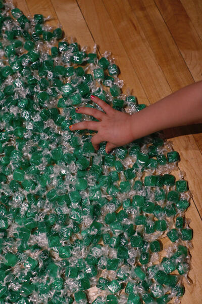 green candies individually wrapped in cellophane. hand reaching out to take one.