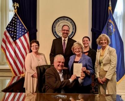 Photographed with Governor Sisolak (seated) are (from left) Mary Doucette, Chad Hensley, Senator Joyce Woodhouse, and lobbyists Lea Cartwright and Jeanette Belz.