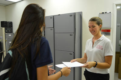 A woman handing papers to a girl student
