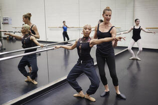 A woman guiding a student in a dance class.