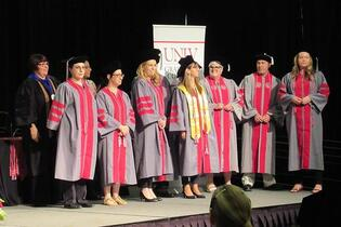 A group of graduates in gray and red gowns and caps.